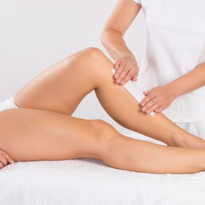 48131577 - midsection of beautician waxing woman's leg at salon