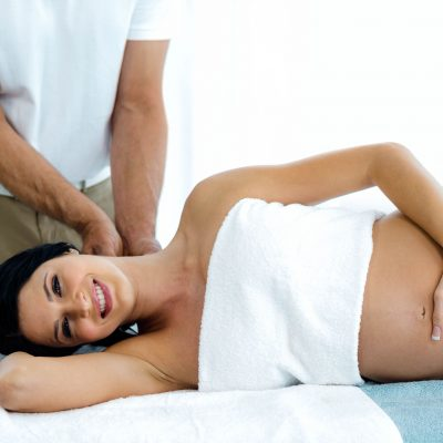 53231281 - pregnant woman receiving a back massage from masseur at home