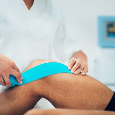56462292 - physical therapist placing kinesio tape on patient's knee